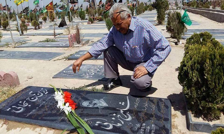 A photo of Mohammad Jarrahi visiting the grave of fellow labor activist Shahrokh Zamani, who died of a stroke in September 2015 after being denied medical care as a political prisoner.